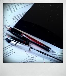 Moleskine notebook and Uniball gel pens